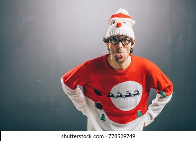 Moody man sticking his tongue out, dressed in funny glasses, christmas sweater and beanie. Christmas concept.