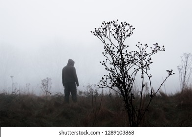A moody out of focus hooded figure standing in the background on a foggy winters day. With a muted edit.