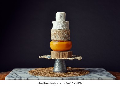 moody photo of a tower of cheese wheels on a slice of wood
