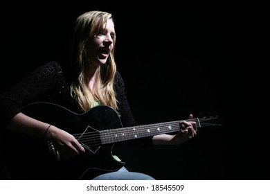moody picture of beautiful woman playing guitar and singing