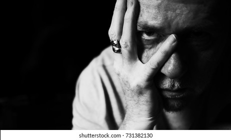 Moody portrait of a middle aged man with stubble peering through fingers.