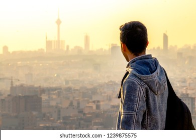 Moody portrait with Tehran skyline at the background. Alone man looking at cityscape of Tehran-Iran at the sunset.