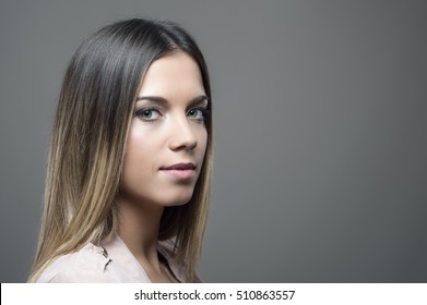 Moody portrait of young beauty looking at camera over the shoulder on gray studio background with copyspace
