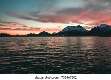 Moody seascape of mountains and ocean with vibrant blue and purple sky
