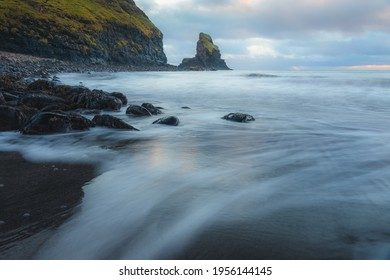 Moody seascape scenery and sea stack during sunrise or sunset at Talisker Bay Beach on the Isle of Skye, Scotland