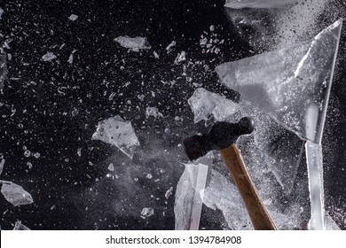 Moody, Shadowy High-Speed Photo of a Ball-Peen Hammer Smashing through a Sheet of Ice - Exploding in a Cloud of Dust and Shards with a Black Background