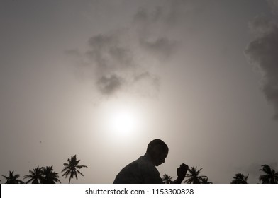Moody silhouette of a young Asian male  Shaolin Kung Fu instructor doing training exercises.The background shows dark grey clouds covering the sun, with silhouetted coconut palm trees.