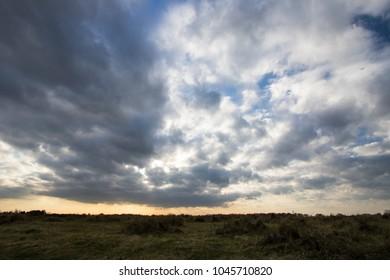 Moody sky cloudscape, Mottled blanket of cloud over barren coastal landscape. Atmospheric sinister weather background image with grassland and sunset horizon..