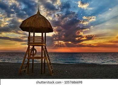 Moody sky sunset, Sunchair Lifeguard tower on caribbean beach, Haiti