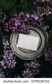 Moody spring wedding stationery mockup scene. Blank greeting card, invitation on vintage silver plate. Purple lilacs flowers and rain drops. Blooming Syringa bush in the garden. Vertical flat lay, top