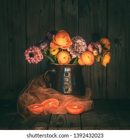 Moody still life with colorful flowers in a jug on a rustic wooden table. Next to it there is a glass of fresh orange juice and a half of citrus fruits. Moody atmosphere. Dark mood photography.