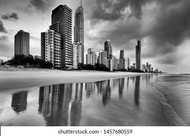 Moody stormy black-white image of Surfers Paradise high-rise towers waterfront with reflection in wet sand of Pacific beach at sunrise.