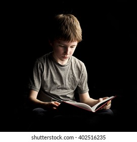 A moody studio shot of a boy reading his book