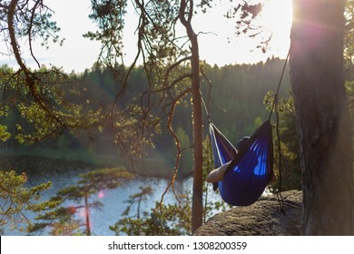 Moody sunset photo of a man in a hammock. Shallow depth of field and a low angle.