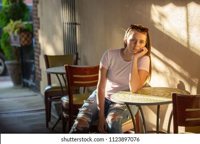 moody teenage girl sitting at a table outside