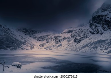Moody winter day in Dolina Gąsienicowa Valley, High Tatra Mountains, Poland. Czarny Staw Gąsienicowy Lake is starting to freeze. Selective focus on the ice, blurred background. - Shutterstock ID 2030273615