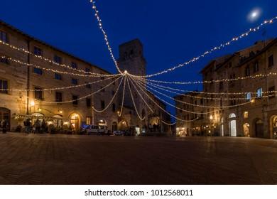 The moon above Piazza della Cisterna in San Gimignano, Siena, Tuscany, Italy