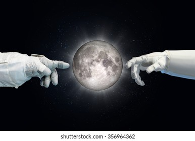 Moon in between astronaut and robotic hand. Elements of this image furnished by NASA.