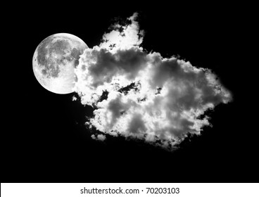 Moon between the clouds in dark nght, a dark night brings a bright, amber moon alive with puffy hazy clouds.