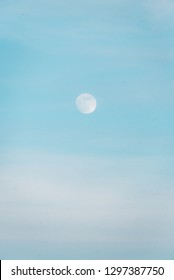 The moon in a blue daytime sky