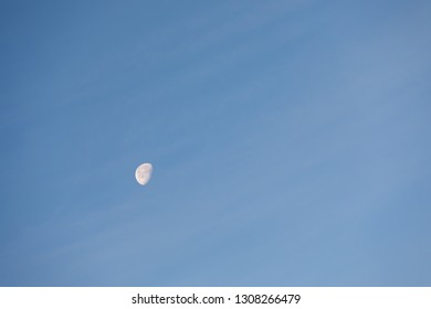 moon with blue sky and slight clouds