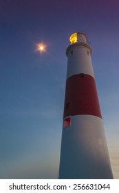 The moon climbs up behind Portland Bill lighthouse just as the last rays of the sun hit the tower