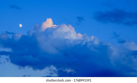 Moon and clouds in the blue sky at sunset and the beginning of the blue hour