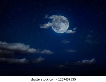 Moon and clouds in the night. Moonlight background. Dark blue backdrop.