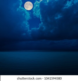 moon in clouds over sea