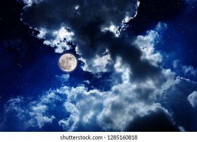 The moon with cloudy night sky with shiny stars for background.