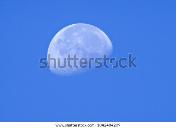 the moon in the day with it being lit from above