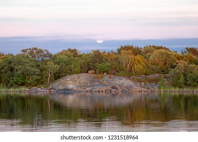 The moon gently rises in the distance behind trees and a rocky shoreline in a cove on the Island of Nicklösa in the Åland Islands, Finland, at sunset a few days after midsummer.