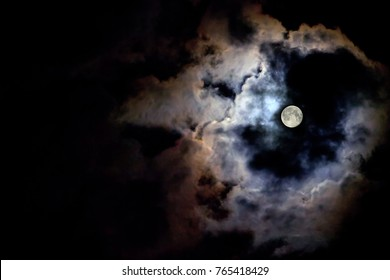 The moon illuminates the black sky around its light at night. Copy space for text. The moon behind the clouds.