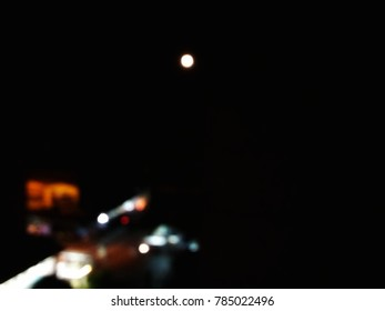 The moon in the midnight sky with city street light below.