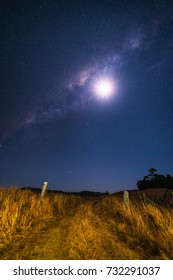 Moon and Milky Way rising over road and farmland