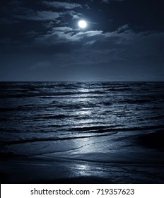 Moon in night sky over moonlit sea water. Travel background.
