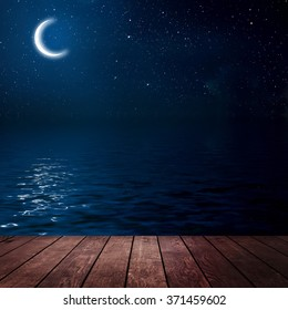 moon on a background star sky reflected in the sea. wood