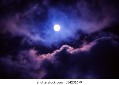 The moon on the dark sky among the clouds, natural abstract background.