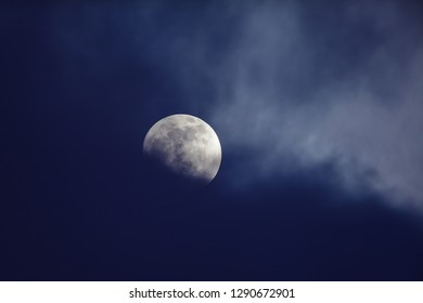 Moon on night sky against dark clouds