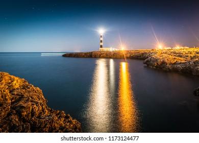 Moon over Artrutx Lighthouse on Minorca Island south western shore, Balearic Islands, Spain.