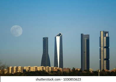 The moon over the four towers in the city of Madrid