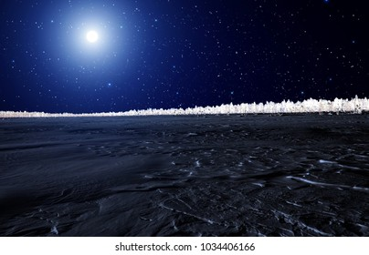 The moon over the frozen forest lake
