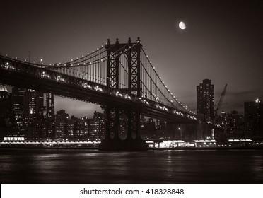 Moon over Manhattan. Silhouette of Manhattan Bridge and Manhattan Skyline at nigh. Old photo stylization, film grain added. Sepia toned