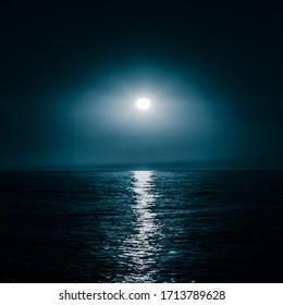 Moon over the sea. Moonlight on the sea. Night sky. A patch of moonlight on the surface of the night sea.