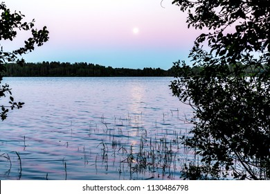 The moon is reflected in the surface of the lake. Beautiful night landscape, background