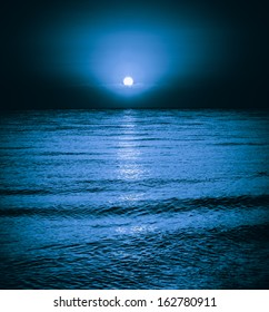 Moon reflecting in a lake sea ocean waves. Moonlight night background