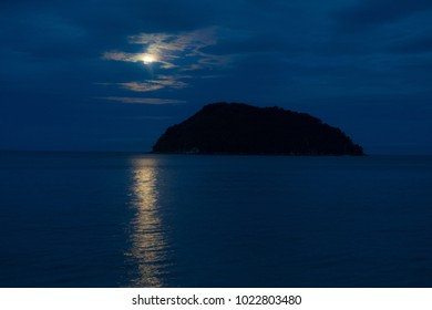 Moon reflecting in water next to an island on the coast of Abel Tasman National Park, New Zealand.