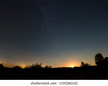 The moon rises on a clear night in the countryside panorama.