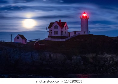 Moon rising behind clouds at dusk at Nubble lighthouse shining brightly, also referred to as Cape Neddick light, in Maine.