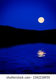 Moon rising over montains at dusk blue light night time